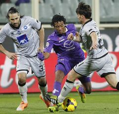 Fiorentina's Juan Guillermo Cuadrado is challenged by Atalanta's Mario Yepes, left, and Luca Cigarini, right, during a Serie A soccer match at the Artemio Franchi stadium in Florence, Italy Saturday Feb. 8 2014. (AP Photo/Fabrizio Giovannozzi)