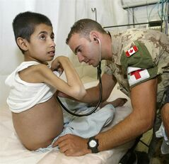 Cpl. Kevin Comeau, 30, of Tabusintac, N.B., listens to the defective heart of Djamshid Popal, 9, at the Canadian military hospital in Kabul, Afghanistan, on Saturday, June 26, 2004. With the benefit of hindsight, Popal — the fragile Afghan child whose life-saving heart procedure in 2004 made headlines across Canada — wishes he had never left the strange country that saved his life.