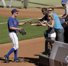 Texas Rangers' David Murphy signs autographs as he leaves the field during the seventh inning of an exhibition spring training baseball game against the Chicago Cubs Wednesday, March 6, 2013, in Surprise, Ariz. (AP Photo/Charlie Riedel)