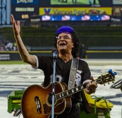 Ides of March lead singer Jim Peterik leads his band in the national anthem at the Chicago White Sox baseball game against the Los Angeles Angels on Monday, June 30, 2014, in Chicago. (AP Photo/Matt Marton)