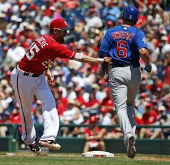 Washington Nationals first baseman Adam LaRoche, left, tags Chicago Cubs' Ryan Sweeney, right, out at first base during the third inning of a baseball game at Nationals Park, Sunday, July 6, 2014, in Washington. Sweeny was called safe, but the play was overturned and he ruled out. (AP Photo/Alex Brandon)