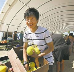 Lunan Zhao holds fresh sugar honey melons at Wenkai Oriental Vegetables in the farmers market.