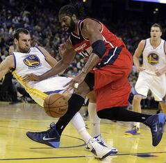 Washington Wizards' Nene Hilario, right, drives the ball into Golden State Warriors' Andrew Bogut (12) during the first half of an NBA basketball game, Tuesday, Jan. 28, 2014, in Oakland, Calif. (AP Photo/Ben Margot)