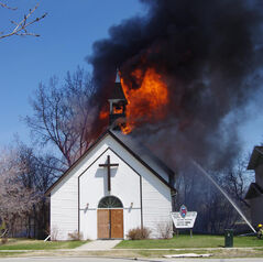 Firefighters aim a stream of water towards the flames breaking through the roof of the United Church in Starbuck.