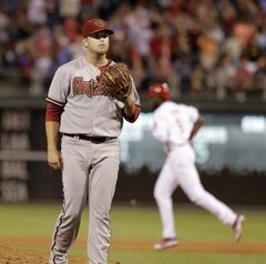 Arizona Diamondbacks Evan Marshall waits for a new ball after Philadelphia Phillies' Domonic Brown hit a two run home run in the seventh inning of a baseball game on Friday, July 25, 2014, in Philadelphia. The Phillies won 9-5. (AP Photo/H. Rumph Jr)