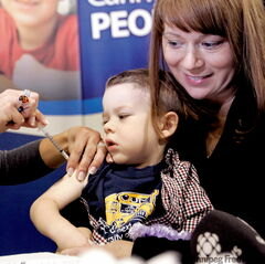 Easton Horbatiuk, with his mom, Tamara, puts on a brave face at the Franco-Manitoban Cultural Centre Monday. The three-year-old was one of 4,000 in Winnipeg who rolled up their sleeves on the first day of the province's mass H1N1 immunization program.