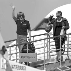 Mayor Shari Decter Hirst waves as she departs the first WestJet Encore plane from Calgary to Brandon Tuesday.