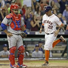 Houston Astros' Carlos Corporan (22) scores behind Texas Rangers catcher Tomas Telis in the seventh inning of a baseball game Saturday, Aug. 30, 2014, in Houston. Corporan scored from third base on a throwing error by pitcher Phil Klein. (AP Photo/Pat Sullivan)