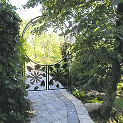 This arched gateway crafted from mild steel by local artist Jake Goertzen features a rounded arch that frames a picturesque view of a perennial garden.