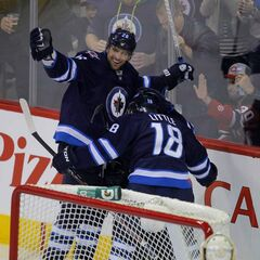 Winnipeg Jets Blake Wheeler (left) and Bryan Little celebrate a goal by captain Andrew Ladd against the New Jersey Devils at the MTS Centre Thursday. The goal came just eight seconds after the opening faceoff.