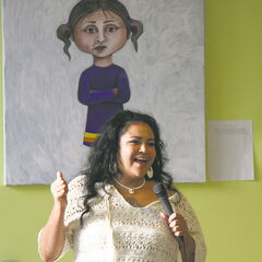 Jackie Traverse speaks at the opening of her show Ever Sick at Neechi Commons, standing in front of a self-portrait.