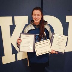 River East Kodiaks forward Cassandra Szczepanski holds certificates commemorating three of her recently-awarded scholarships.