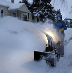 Darlene Lewis clears snow around her home on Winston Road this morning,
