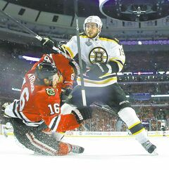 Bruins centre Tyler Seguin (19) bowls over Blackhawks' Marcus Kruger (16) Saturday.