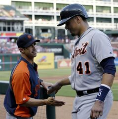 Detroit Tigers manager Brad Ausmus congratulates Victor Martinez (41) after Martinez and Nick Castellanos scored on a single by Austin Jackson in the third inning of a baseball game against the Texas Rangers, Thursday, June 26, 2014, in Arlington, Texas. (AP Photo/Tony Gutierrez)