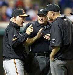 Baltimore Orioles manager Buck Showalter, left to right, argues with home plate umpire Dana DeMuth and first base umpire Ron Kulpa in the eighth inning of a baseball game, Friday, Aug. 15, 2014, in Cleveland. Showalter was arguing whether Adam Jones was hit by a pitch. (AP Photo/Tony Dejak)