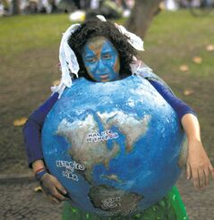 Environmental activists, one portraying a shrinking planet, attend a protest on the final day of the United Nations Conference on Sustainable Development.