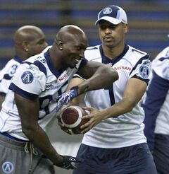 Toronto Argonauts quarterback Cleo Lemon hands off to defensive end Ejiro Kuale during a practice in November 2010 in Montreal.