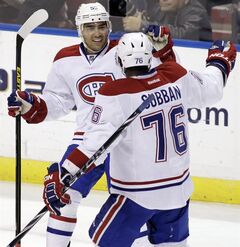 Montreal Canadiens' Francis Bouillon, left, celebrate with teammate P.K. Subban (76) after scoring a goal against the Florida Panthers during the second period of an NHL hockey game on Sunday, March 10, 2013, in Sunrise, Fla. (AP Photo/Luis M. Alvarez)