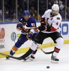 Ottawa Senators' Chris Phillips, right, and New York Islanders' John Tavares chase the puck during the second period of an NHL hockey game Tuesday, March 19, 2013, in Uniondale, N.Y. (AP Photo/Seth Wenig)