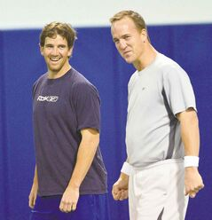 Eli Manning and his brother Peyton laugh as they run through warm up exercises at Duke's Pascal Field House in Durham, North Carolina, Thursday, April 11, 2013. (Chuck Liddy/Raleigh News & Observer/MCT)