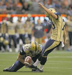 Winnipeg Blue Bombers� Lirim Hajrullahu, right, kicks a field goal as quarterback Brian Brohm holds during the first half of a CFL football game against the B.C. Lions in Vancouver, B.C., on Friday July 25, 2014. THE CANADIAN PRESS/Darryl Dyck