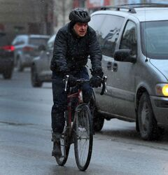 A cyclist on Portage Avenue contends with light snow Thursday morning.