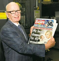 Rupert Murdoch holds the first edition of The Sun on Sunday as it comes off the press in February.