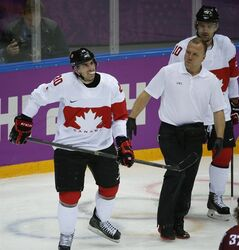 Canada forward John Tavares skates off the ice with a trainer after sustaining a leg injury during the second period of a men's quarterfinal ice hockey game against Latvia at the 2014 Winter Olympics, Wednesday, Feb. 19, 2014, in Sochi, Russia. Tavares is out for the rest of the Olympics. (AP Photo/Mark Humphrey)