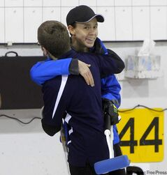 Kyle Doering (left) hugs Lucas Van Den Bosch after clinching the Provincial Curling Men's Curling Championship final.