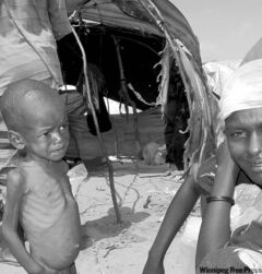 A malnourished child pleads for food in front of his family's makeshift shelter in Mogadishu.