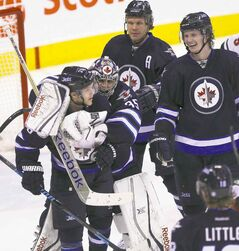 Jets goalie Al Montoya hugs teammate Tobias Enstrom as Olli Jokinen (rear left) and Jacob Trouba (right) look on.
