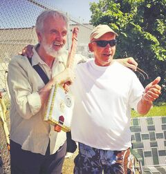 Fred Penner (left) poses with his new cigar-box guitar and its maker, Seepish.