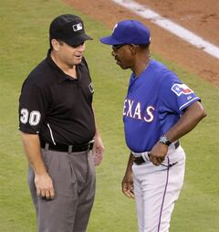 Texas Rangers manager Ron Washington challenges a call with first base umpire Rob Drake during the second inning of a baseball game against the Kansas City Royals Monday, Sept. 1, 2014, in Kansas City, Mo. (AP Photo/Charlie Riedel)