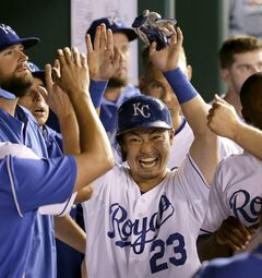 Kansas City Royals' Norichika Aoki, from Japan, celebrates in the dugout after scoring on a single by Alcides Escobar during the seventh inning of a baseball game against the Oakland Athletics, Monday, Aug. 11, 2014, in Kansas City, Mo. (AP Photo/Charlie Riedel)
