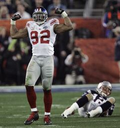 FILE - In this Feb. 3, 2008 file photo, New York Giants defensive end Michael Strahan (92) celebrates after sacking New England Patriots quarterback Tom Brady (12) during the Super Bowl XLII football game in Glendale, Ariz. Strahan was the leader of a defense that stunned the undefeated Patriots in the 2008 Super Bowl. (AP Photo/David Duprey, File)