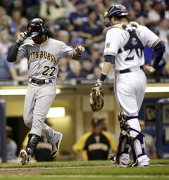 Pittsburgh Pirates' Andrew McCutchen, left, crosses the plate after hitting a home run against the Milwaukee Brewers during the fifth inning of a baseball game Friday, Aug. 22, 2014, in Milwaukee. (AP Photo/Darren Hauck)