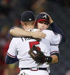 Atlanta Braves third baseman Chris Johnson, right, hugs first baseman Freddie Freeman (5) after defeating St. Louis Cardinals 2-1 in a baseball game, Tuesday, May 6, 2014, in Atlanta. (AP Photo/John Bazemore)