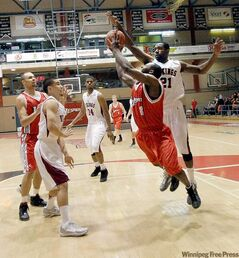 Craig Sharpe (8) of the Winnipeg Wesmen is rejected by Sekani  Milligen of the Valley City State University Vikings Thursday night.