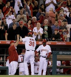 Los Angeles Angels starting pitcher Jered Weaver is greeted in the dugout after getting out of the top of the eight inning with the bases loaded against the New York Yankees during a baseball game in Anaheim, Calif., Monday, May 5, 2014. (AP Photo/Chris Carlson)