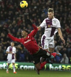 Aston Villa's Nathan Baker, right, heads the ball from Cardiff City's Fraizer Campbell during their English Premier League match at the Cardiff City Stadium, Cardiff Tuesday Feb. 11, 2014. (AP Photo/Nick Potts/PA) UNITED KINGDOM OUT NO SALES NO ARCHIVE