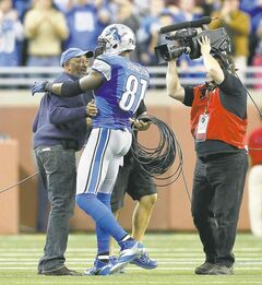 Detroit Lions wide receiver Calvin Johnson hugs his father in the fourth quarter after breaking Jerry Rice's single-season receiving record on the 10th of his 11 catches Saturday against the Falcons.