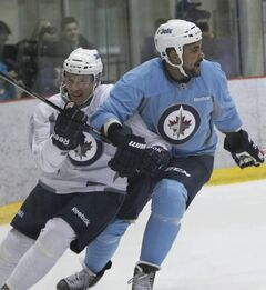 Dustin Byfuglien leans on teammate Antti Miettinen during Wednesday's practice at the MTS Iceplex.