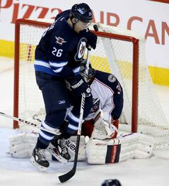 Jets' Blake Wheeler gets in the face of Columbus Blue Jackets' goaltender Curtis McElhinney Saturday in Winnipeg. Wheeler says firing coach Claude Noel should be a 'wake-up call' for the underperforming Jets.