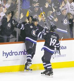 Winnipeg's Blake Wheeler (left) celebrates with Jim Slater after Wheeler scored to give the Jets a 2-1 lead late in the second period.