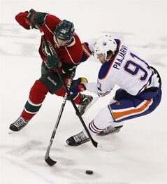 Minnesota Wild defenseman Jonas Brodin (25), of Sweden, battles for possession against Edmonton Oilers left wing Magnus Paajarvi (91), of Sweden, during the first period of an NHL hockey game Sunday March 3, 2013 in St. Paul, Minn. (AP Photo/Genevieve Ross)
