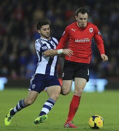 West Bromwich Albion's Shane Long, left, tackles Cardiff City's Jordon Mutch during the English Premier League soccer match at The Cardiff City Stadium, Cardiff, Saturday Dec. 14, 2013. (AP Photo/PA, Nick Potts) UNITED KINGDOM OUT NO SALES NO ARCHIVE