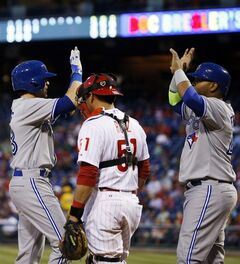 Toronto Blue Jays' Colby Rasmus, left, and Juan Francisco, right, celebrate past Philadelphia Phillies catcher Carlos Ruiz after Rasmus' two-run home run during the fourth inning of a baseball game, Tuesday, May 6, 2014, in Philadelphia. (AP Photo/Matt Slocum)
