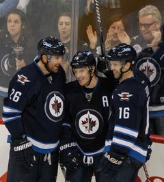 Winnipeg Jets Blake Wheeler (left), Bryan Little (centre) and Andrew Ladd celebrate Little's second goal of the game in the third period to put the Jets ahead 5-0 against the Nashville Predators at MTS Centre.
