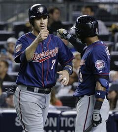 Minnesota Twins' Joe Mauer (7) is greeted by teammate Eduardo Nunez (9) after scoring on a base hit by Kurt Suzuki during the eighth inning against the New York Yankees, Friday, May 30, 2014, in New York. The Twins won 6-1. (AP Photo/Julie Jacobson)